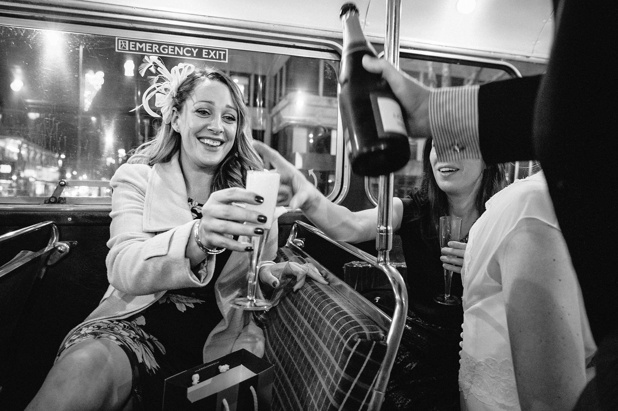 wedding guests enjoy drinks on a London bus