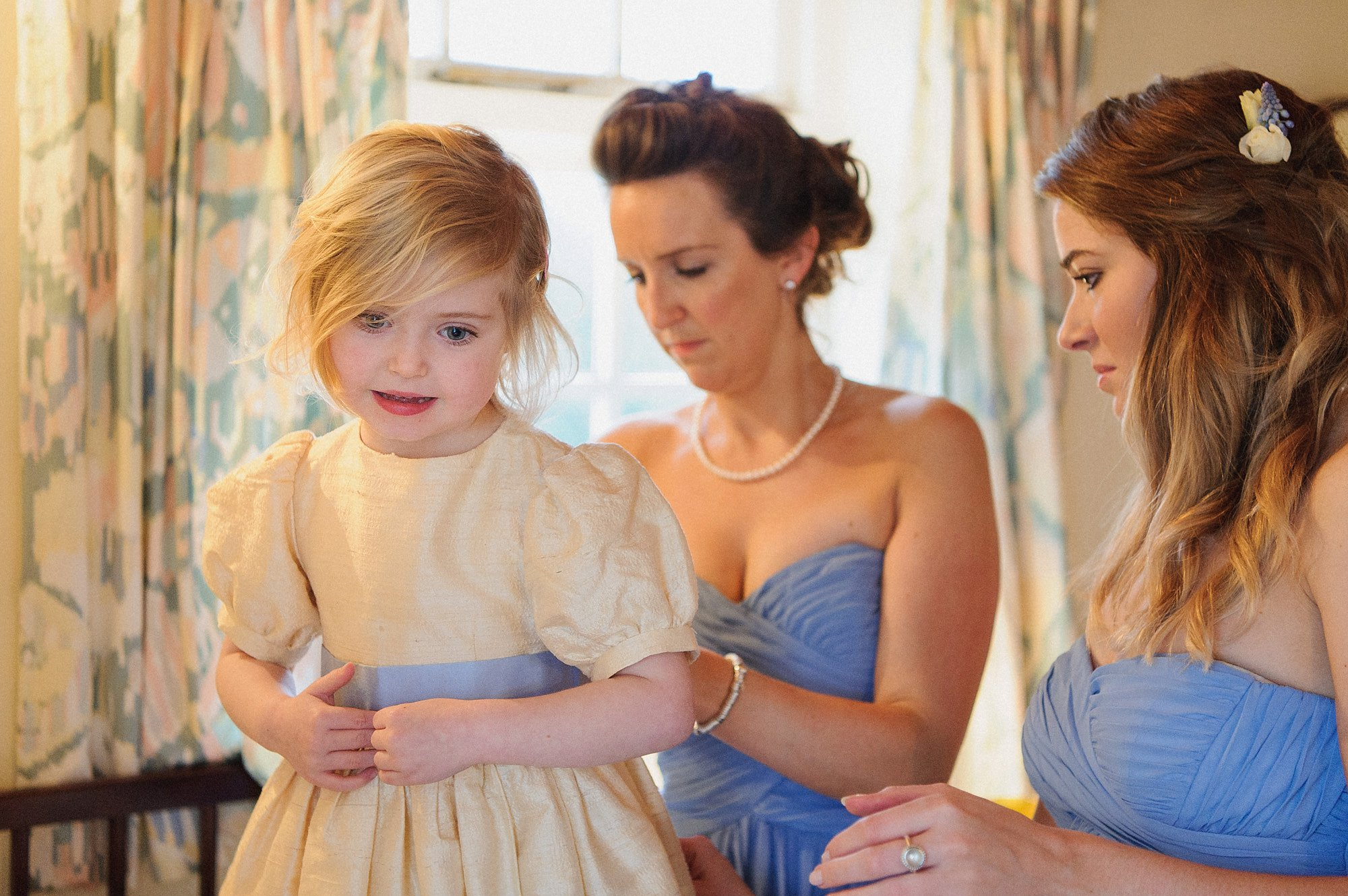 brides maids help the flower girl into her dress
