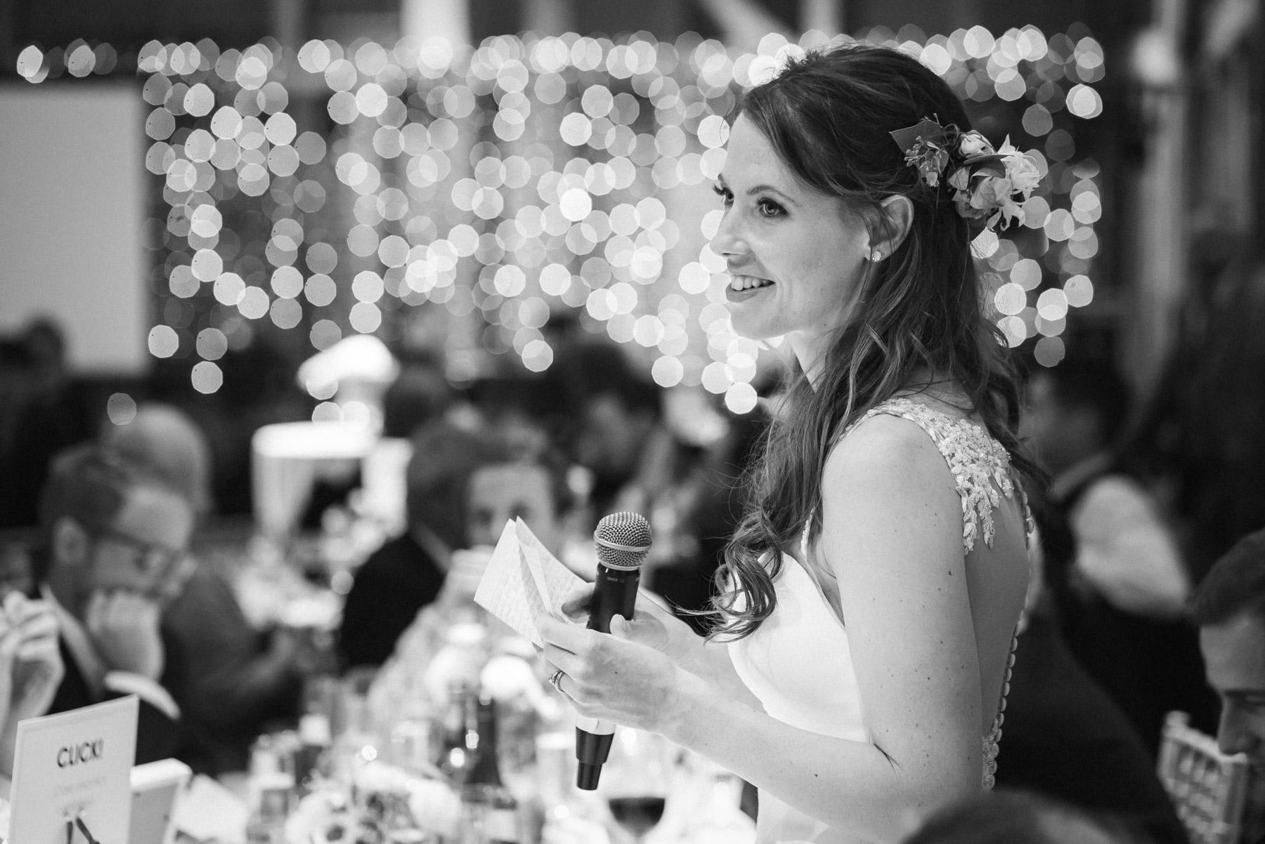 the bride gives a speech at her wedding