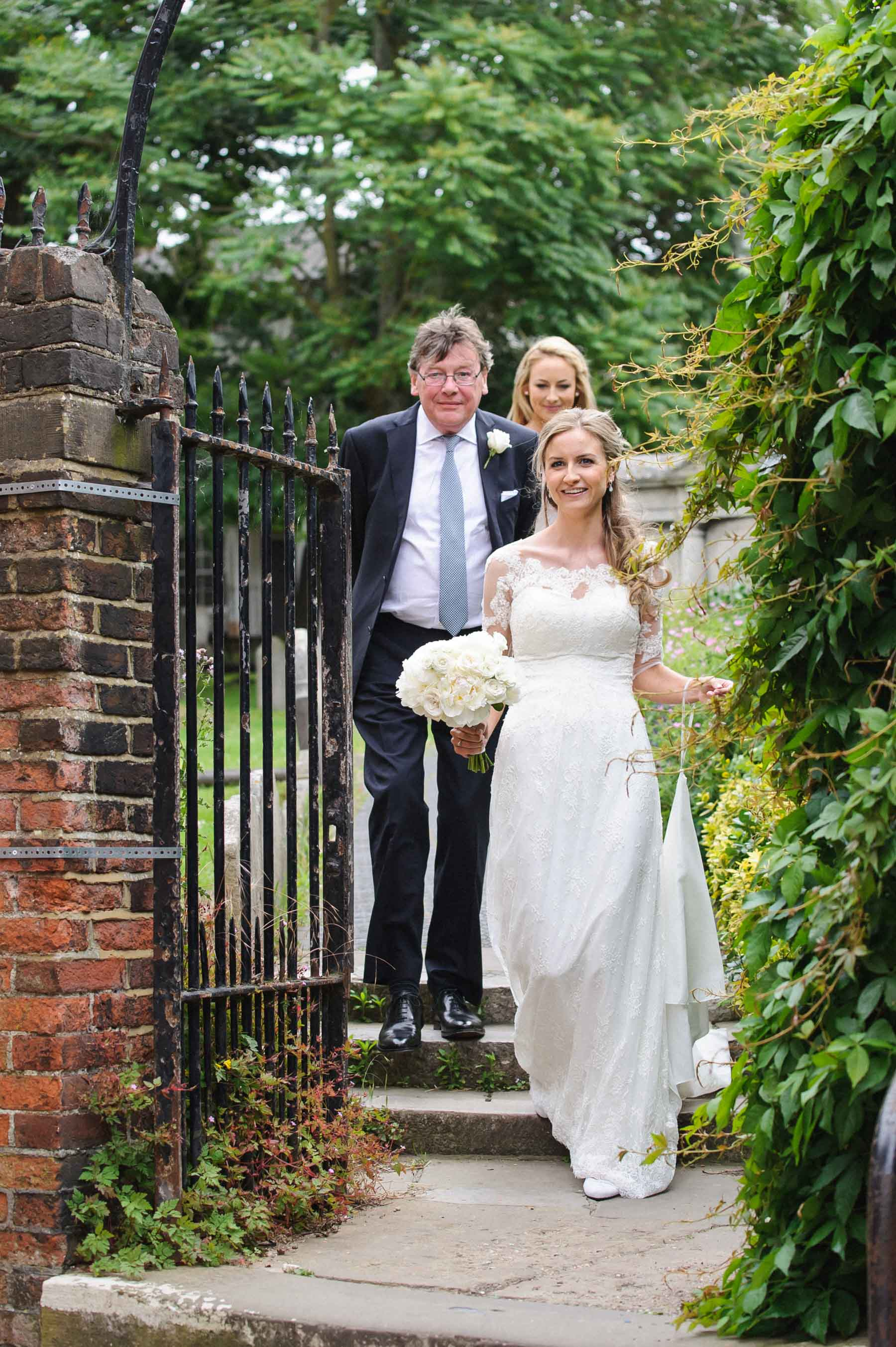 The beautiful bride arrives with her father at Holy Trinity Church Guildford