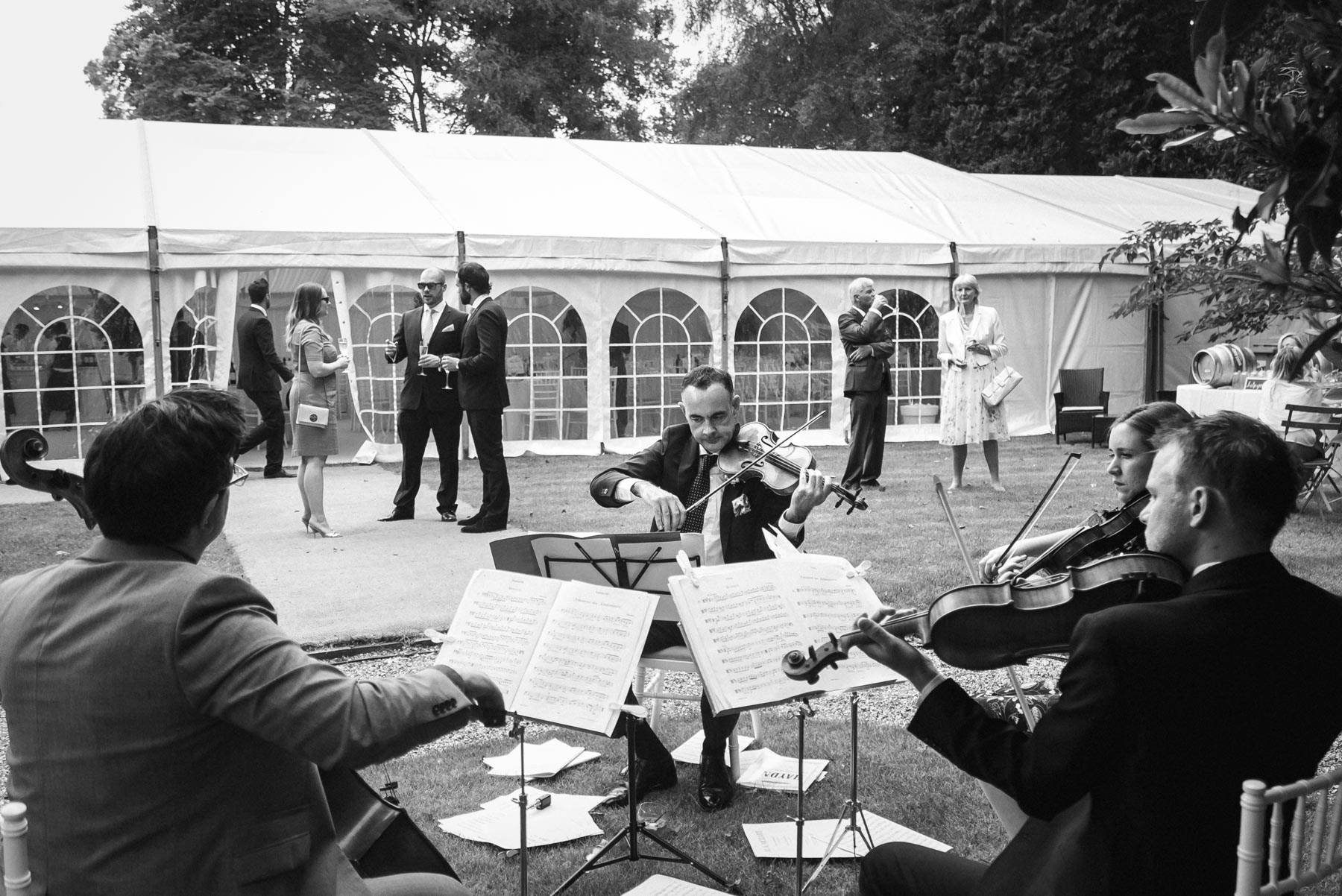 a string quartet playing during the wedding reception in woking