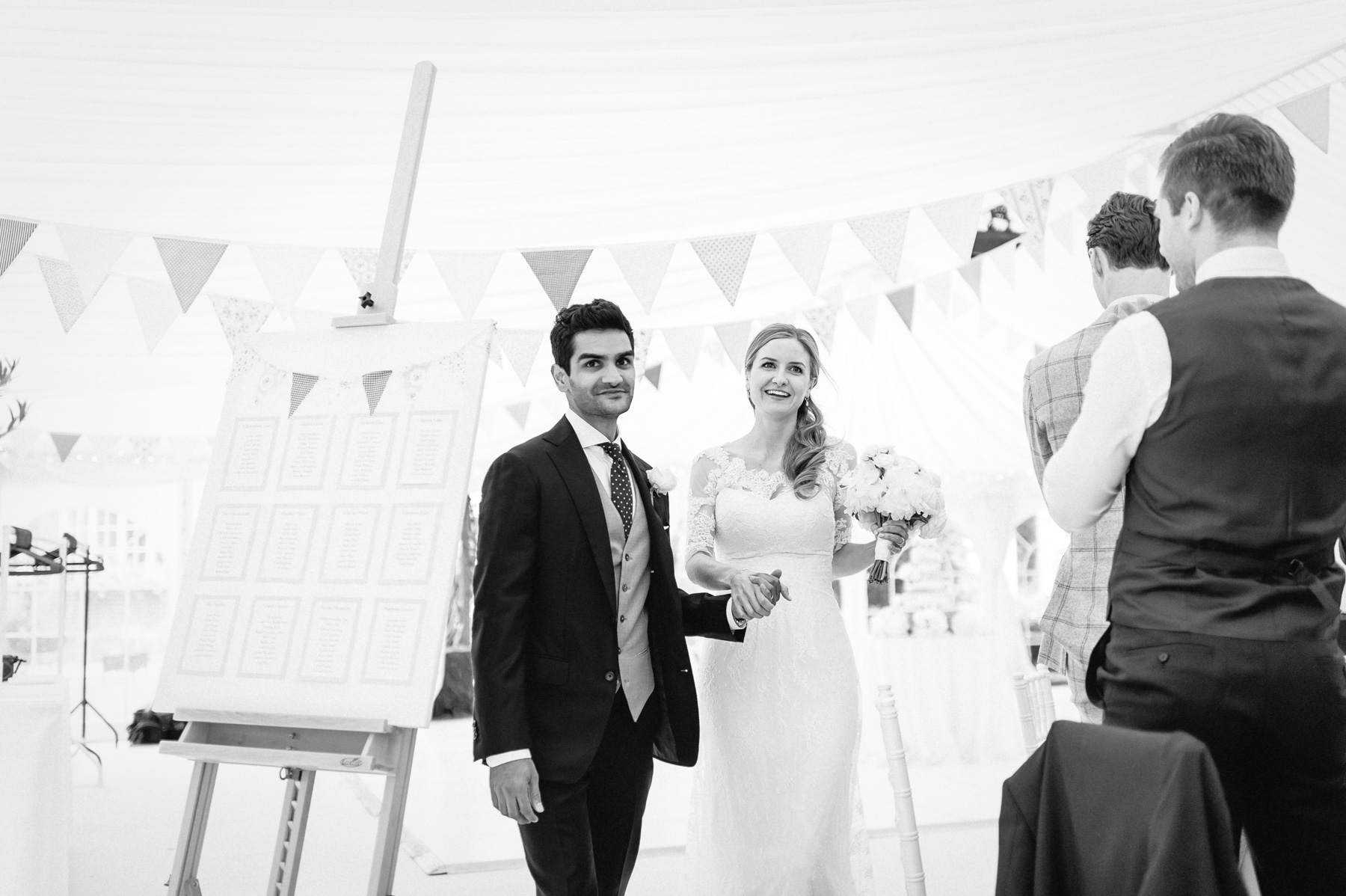 the entrance of the bride and groom to the marquee at their reception in the back garden