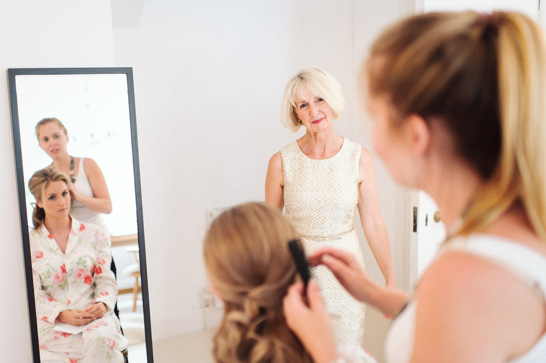 the mother of the bride looks on during the makeup session